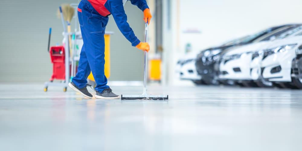 A importância da limpeza industrial: homem limpando o chão de um centro automotivo.