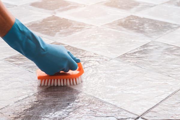 A importância da limpeza industrial: profissional esfregando o chão.