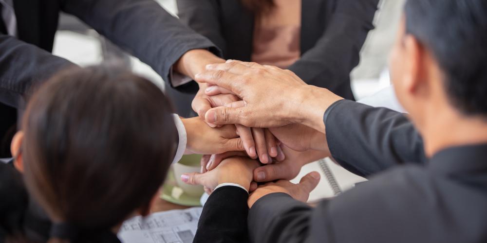 Gestão de mudanças: várias pessoas apertando as mãos.
