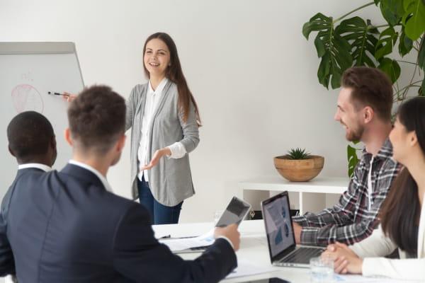Gestão de Pessoas: Coordenadora fazendo uma apresentação para os colegas de trabalho.