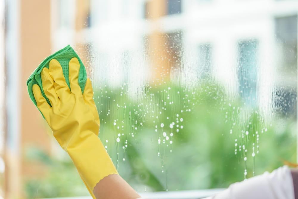 Limpeza de fachada: mulher limpando uma porta de vidro.