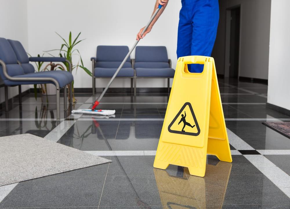 Terceirização de Serviços: homem passando o pano no chão e uma placa de aviso sobre piso escorradio.